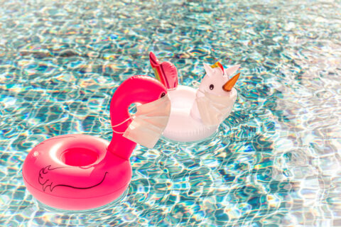 Swimming pool toys unicorn and flamingo in a medical face mask. Concept of Coronavirus outbreak impact on a travel industry for summer season 2020